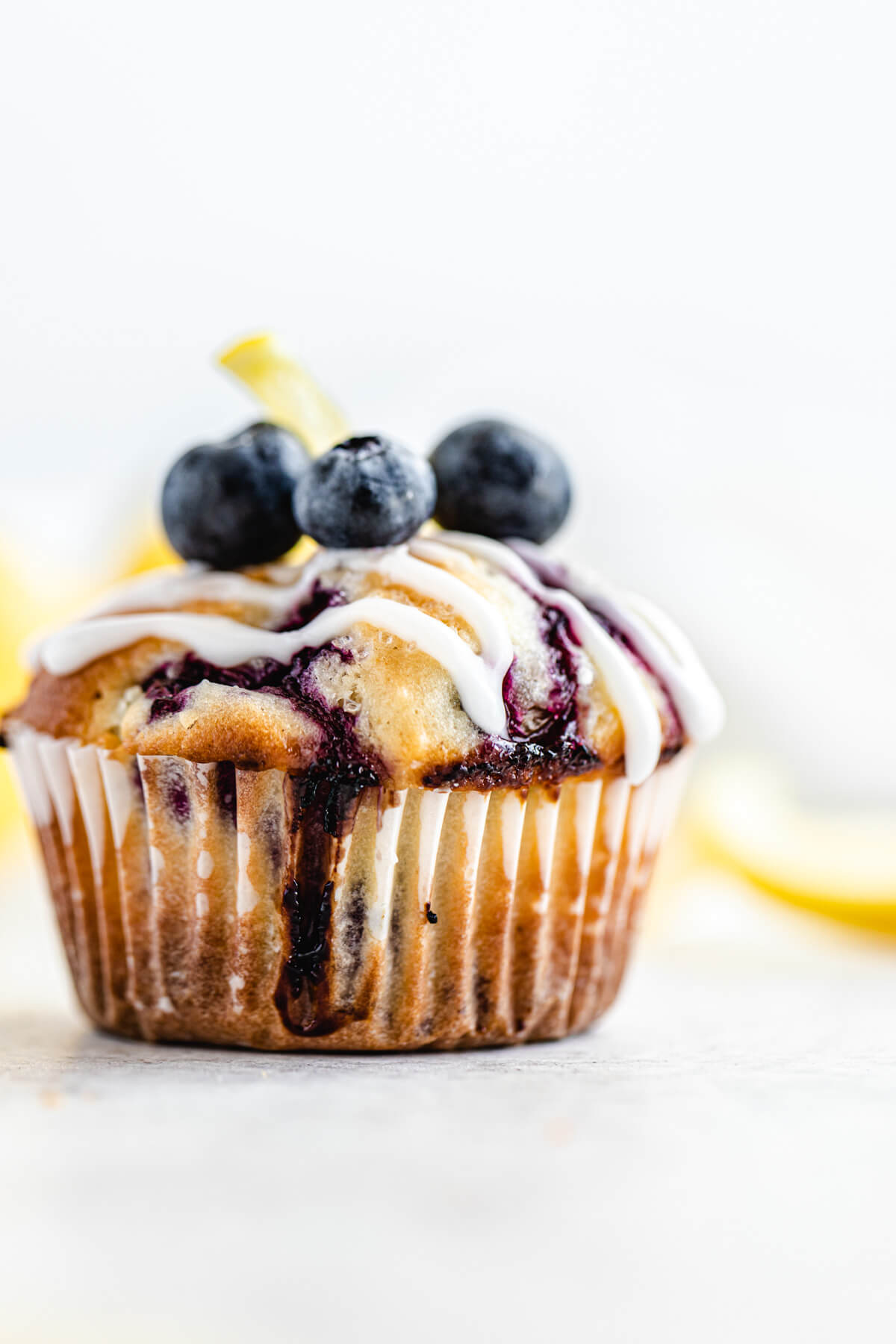 close up of muffin topped with lemon glaze and fresh blueberries