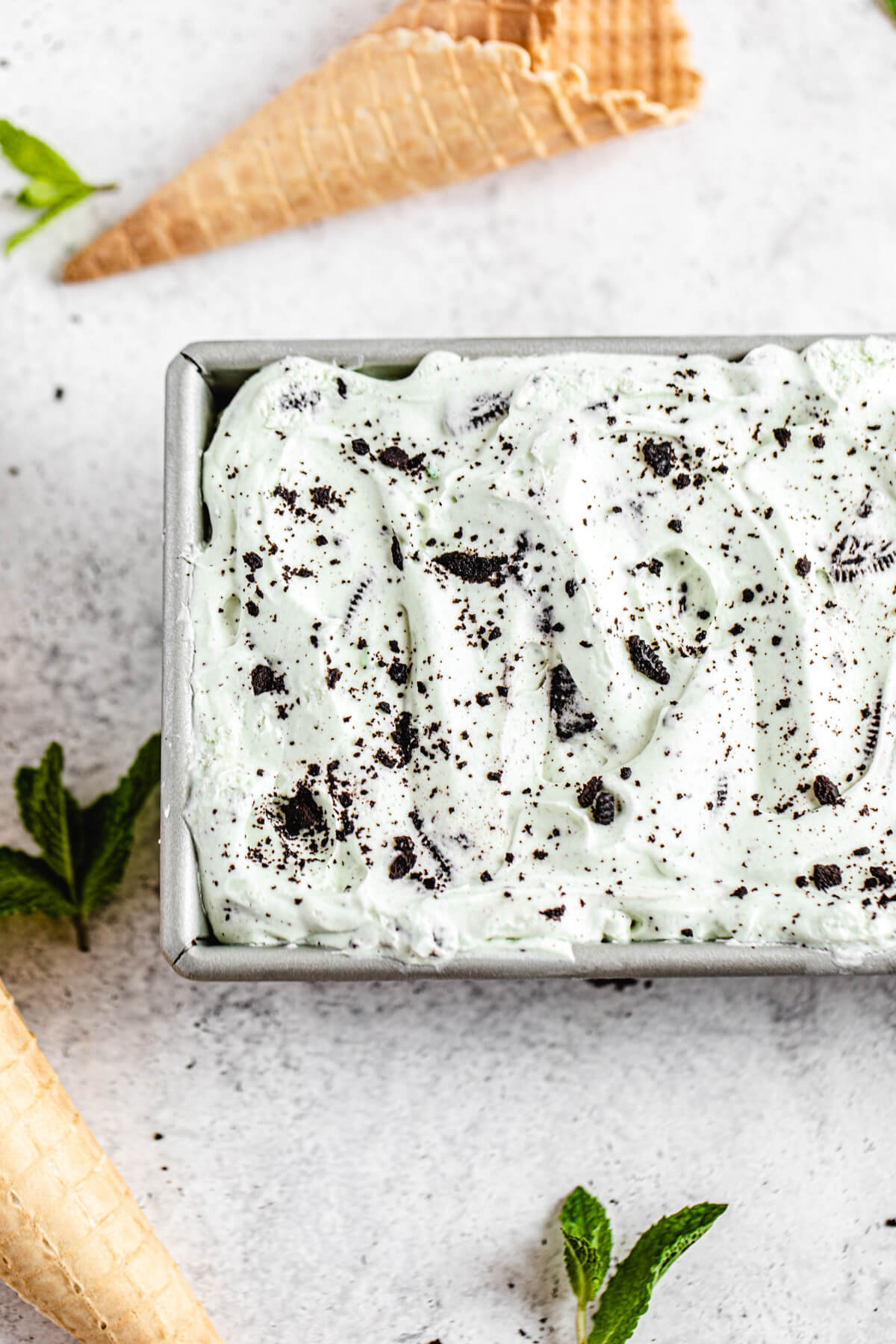 ice cream in a loaf pan with mint leaves and waffle cones around it