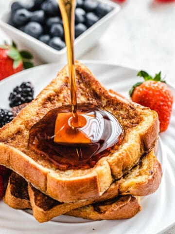 pouring maple syrup onto French toast on a white plate