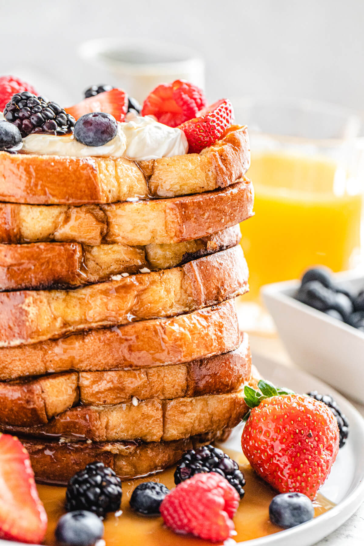 tall stack of French toast topped with whipped cream and fresh fruit