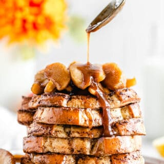 close up spooning syrup onto a stack of French toast on a plate