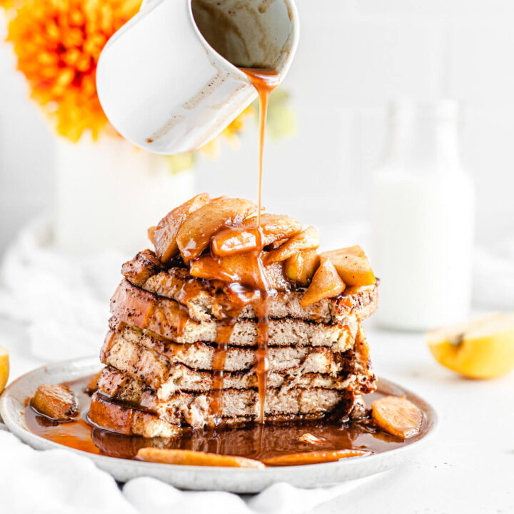 pouring syrup onto sliced stack of French toast