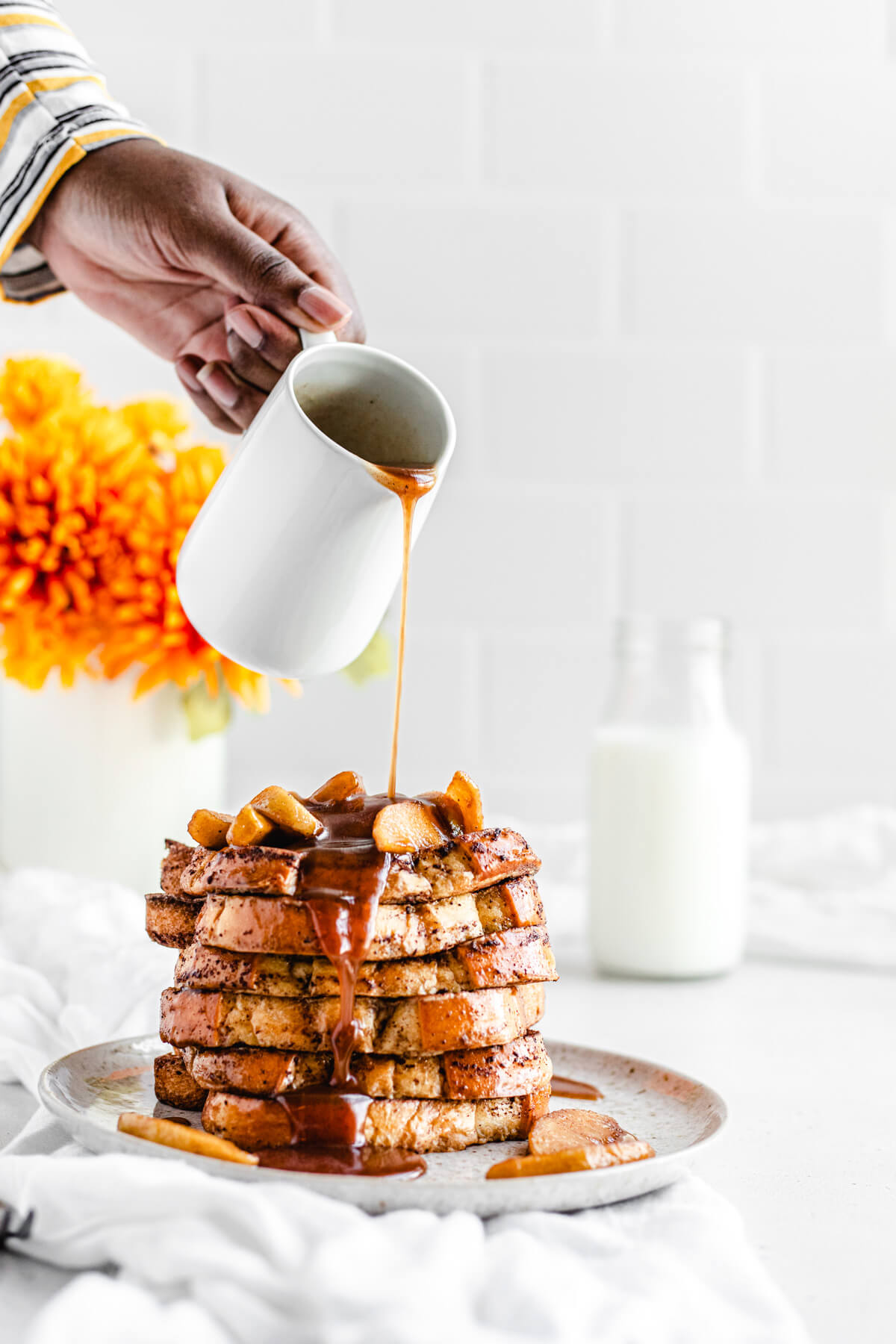 pouring syrup onto a stack of French toast topped with apples