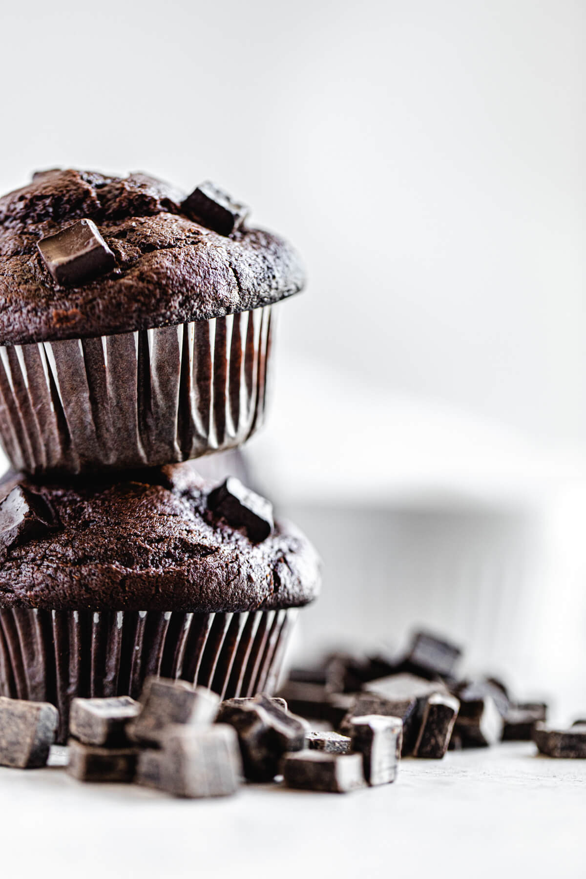 two muffins stacked with chocolate chunks surrounding them