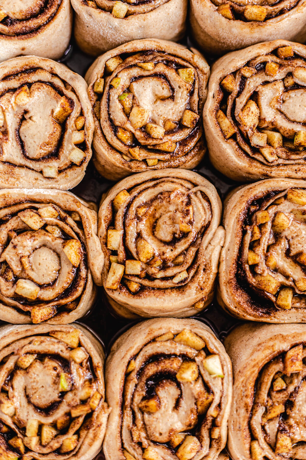 close up of unbaked apple filled cinnamon rolls in a dish