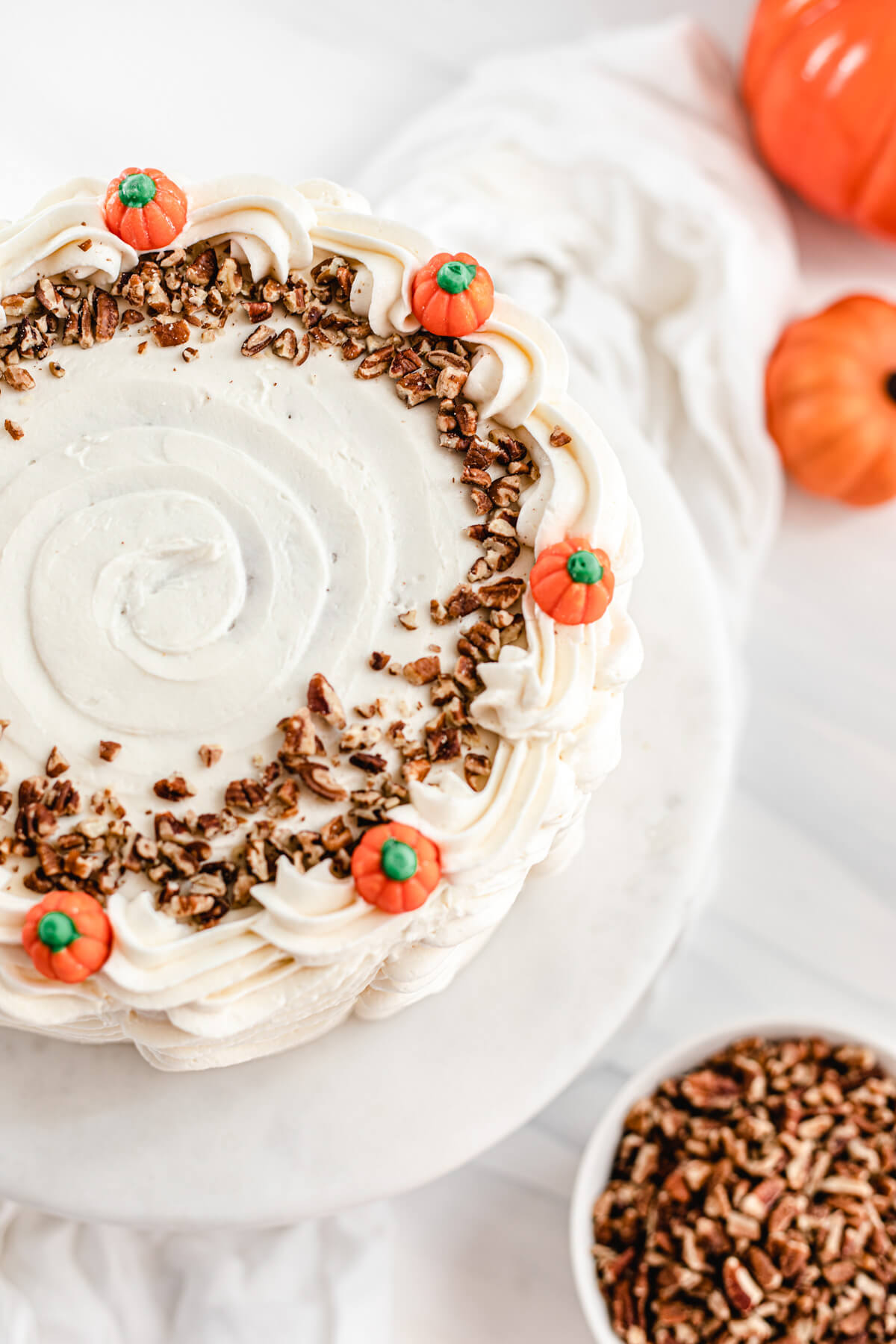 top view of cake decorated with chopped pecans and pumpkin candies