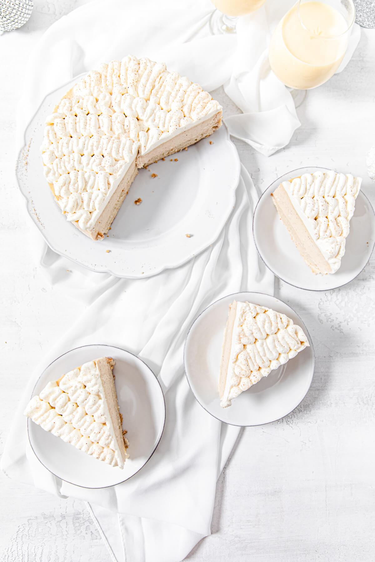 top view of cheesecake on a platter with three slices in three small white plates