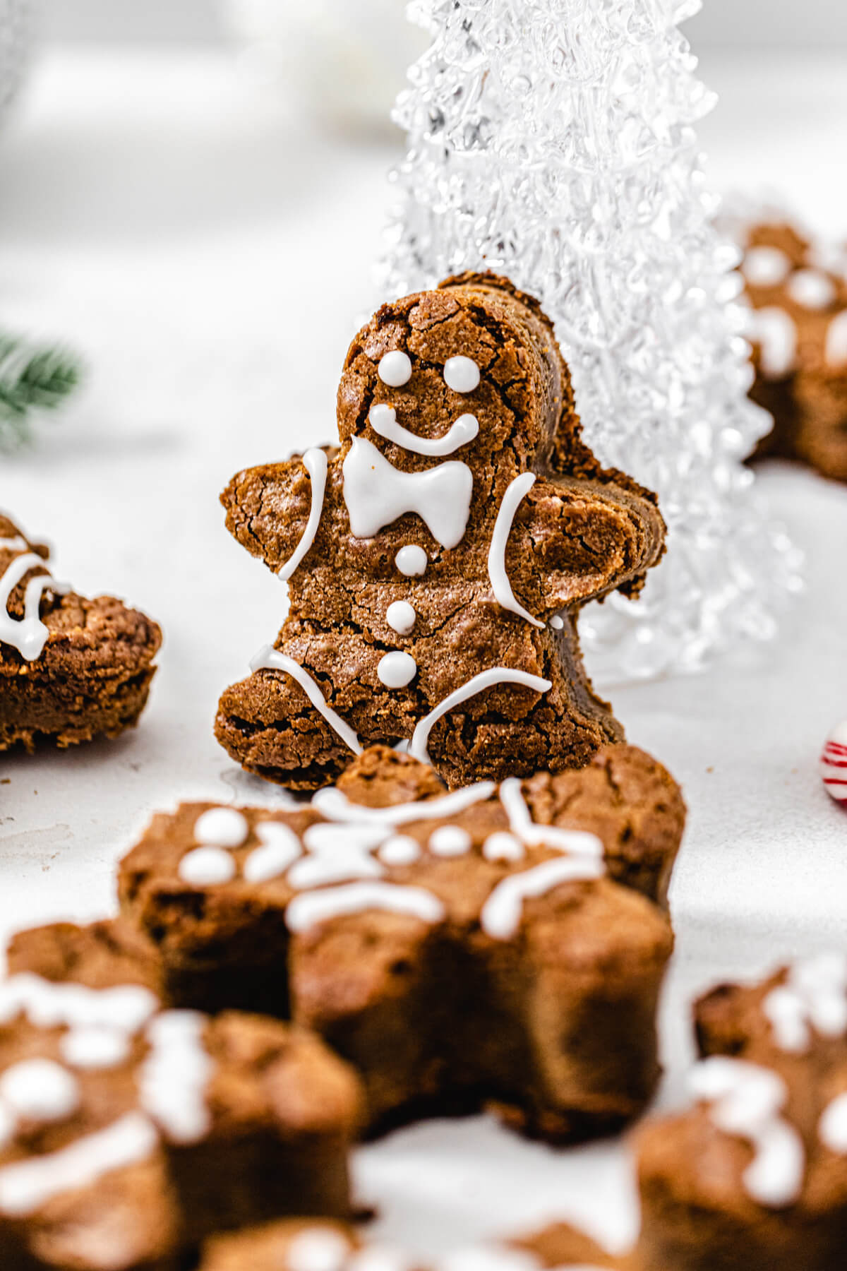 close up of gingerbread man propped onto glass Christmas tree
