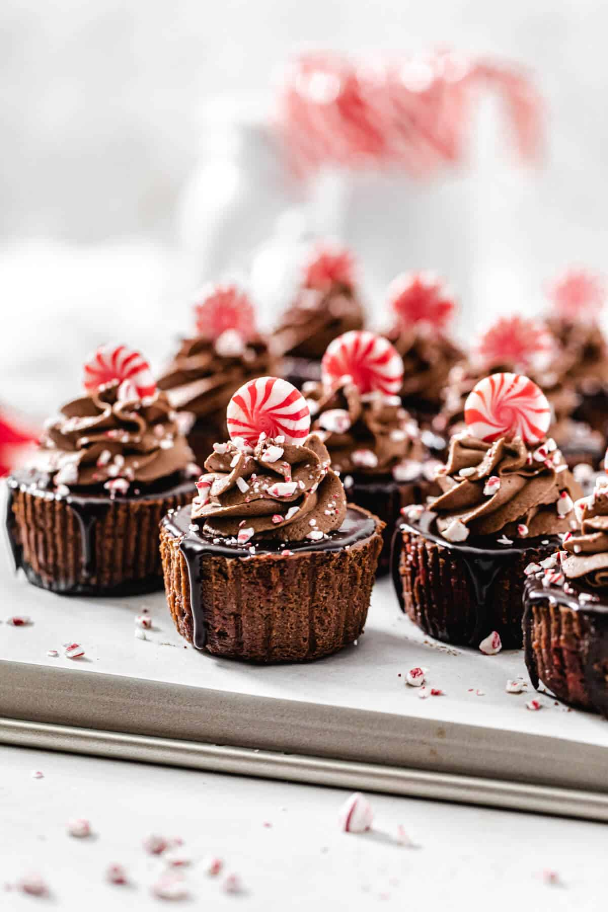 mini cheesecakes on a baking sheet with candy canes in the background