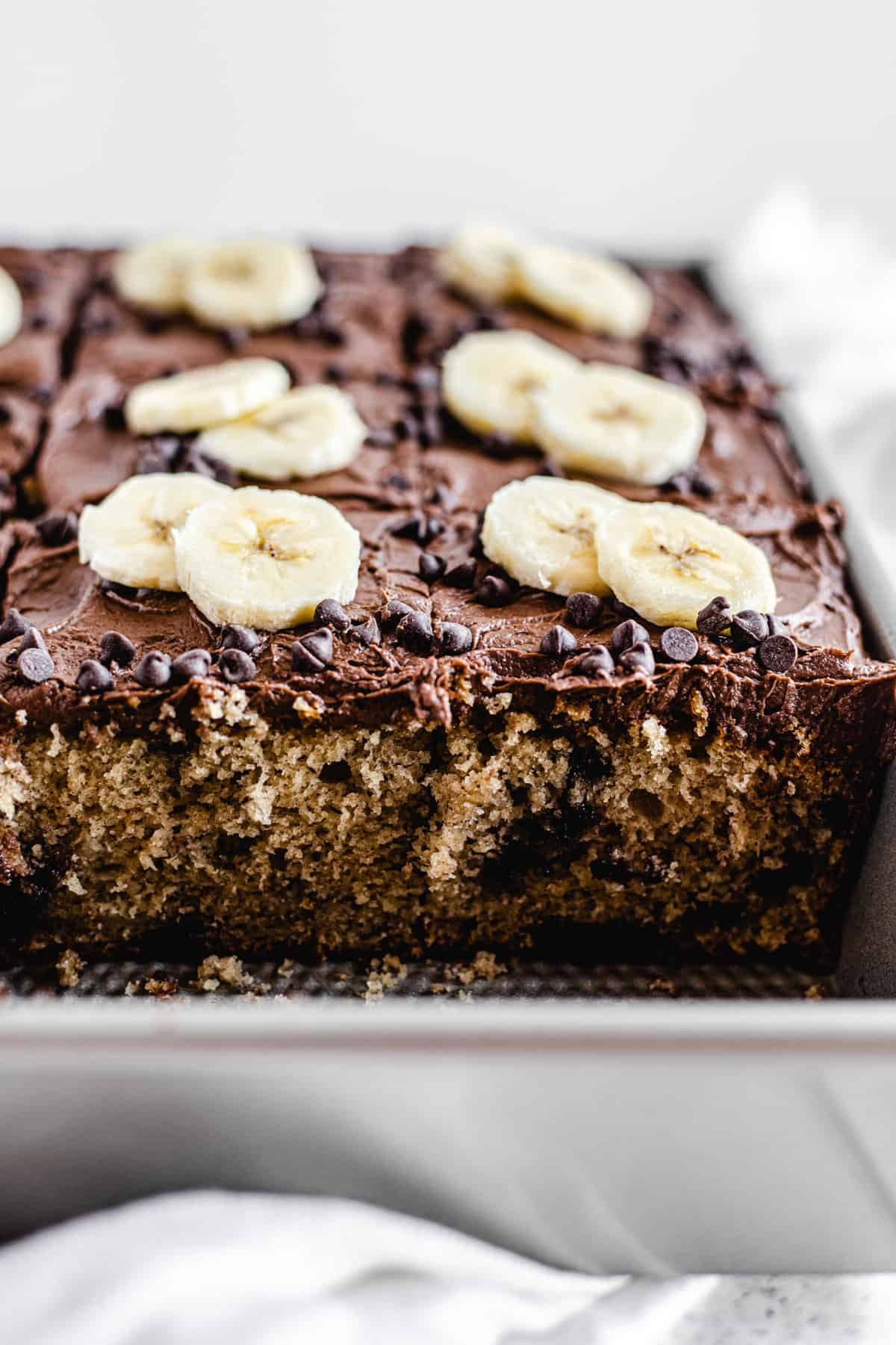 cake topped with chocolate frosting and banana slices in a rectangular cake pan
