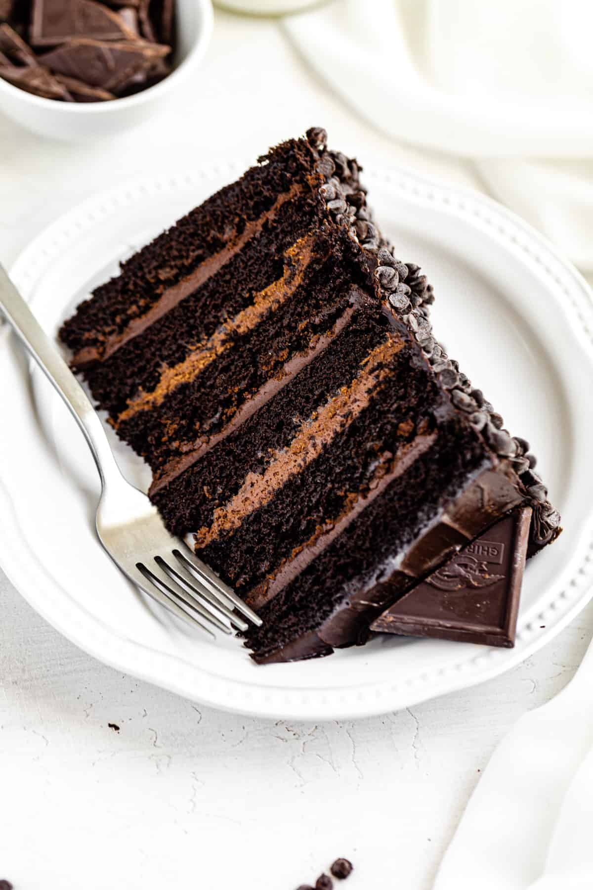 6-layer cake on a white plate with a fork next to it