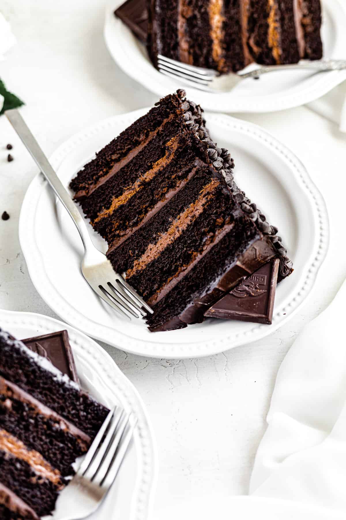 three slices of cake on white plates with a fork beside it