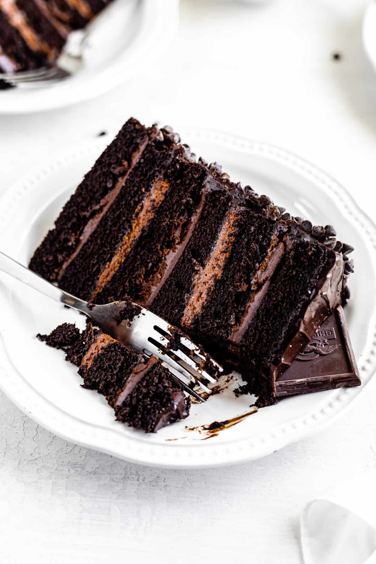slice of chocolate cake on a white plate with fork taking a piece off
