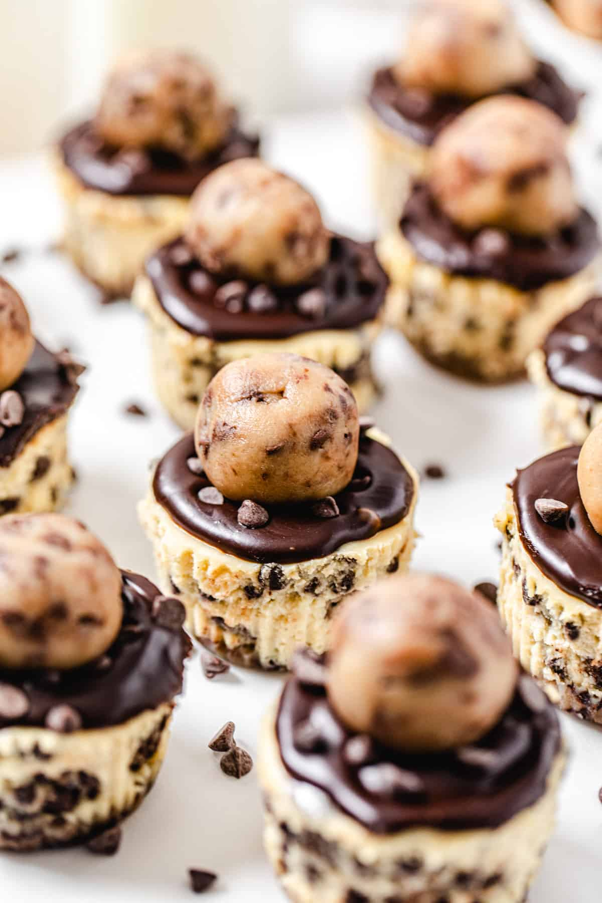 multiple mini cookie dough topped cheesecakes with mini chocolate chips scattered around them