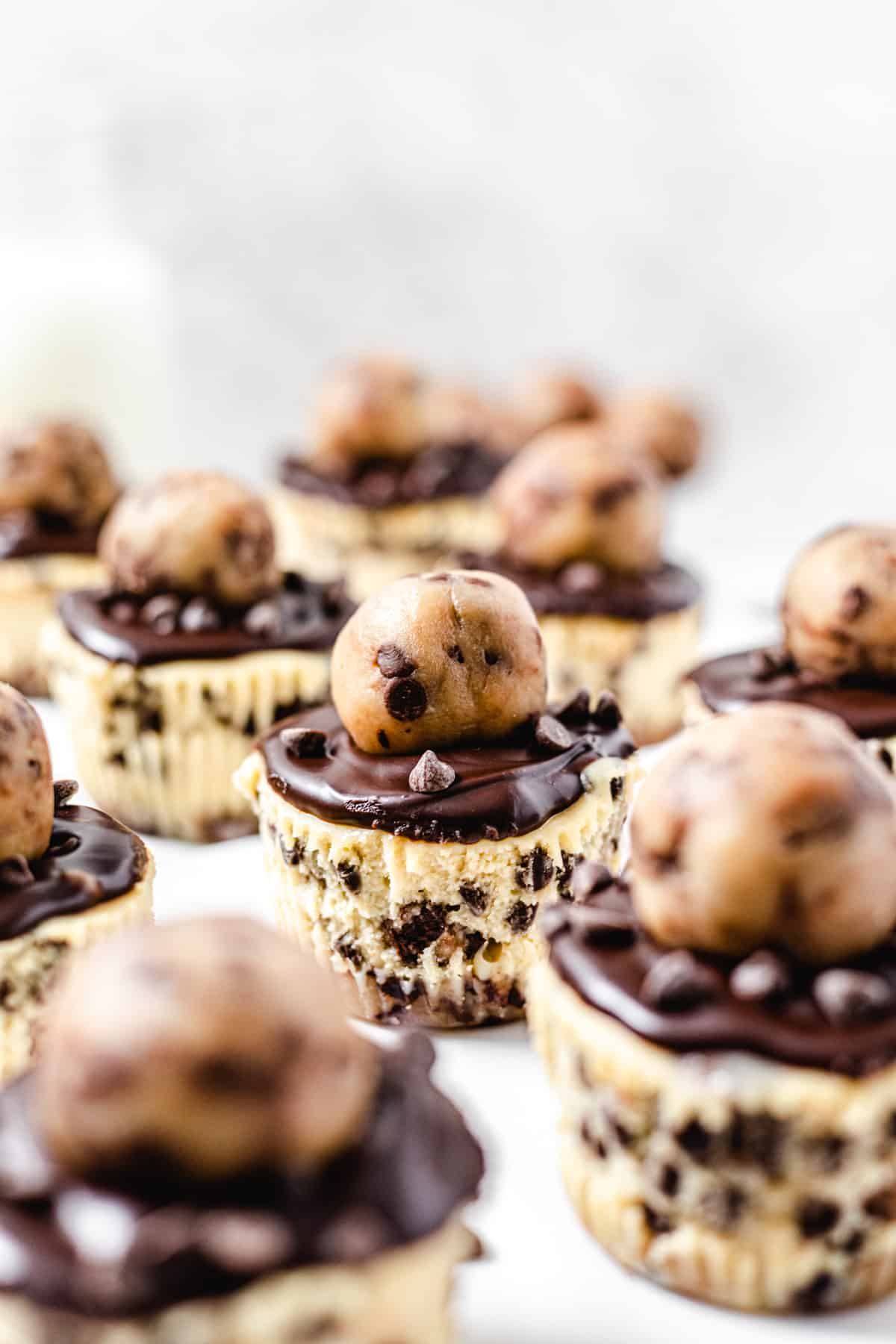 cookie dough topped cheesecake cupcake in the middle of many other cheesecakes