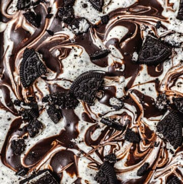 close up of the top of ice cream swirled with ganache and topped with Oreo pieces