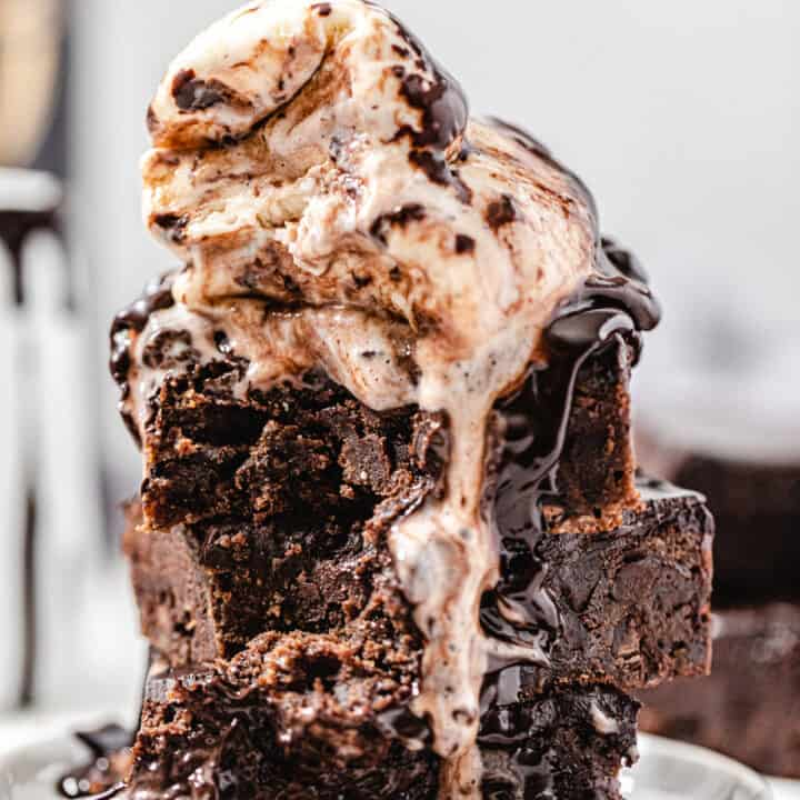 stack of brownies topped with two scoops of vanilla ice cream