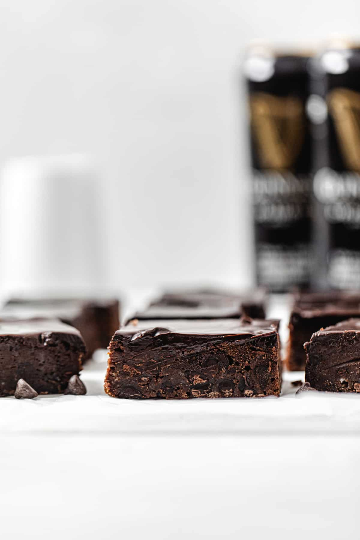 rows of brownies on parchment paper with 2 cans of Guinness beer in the background