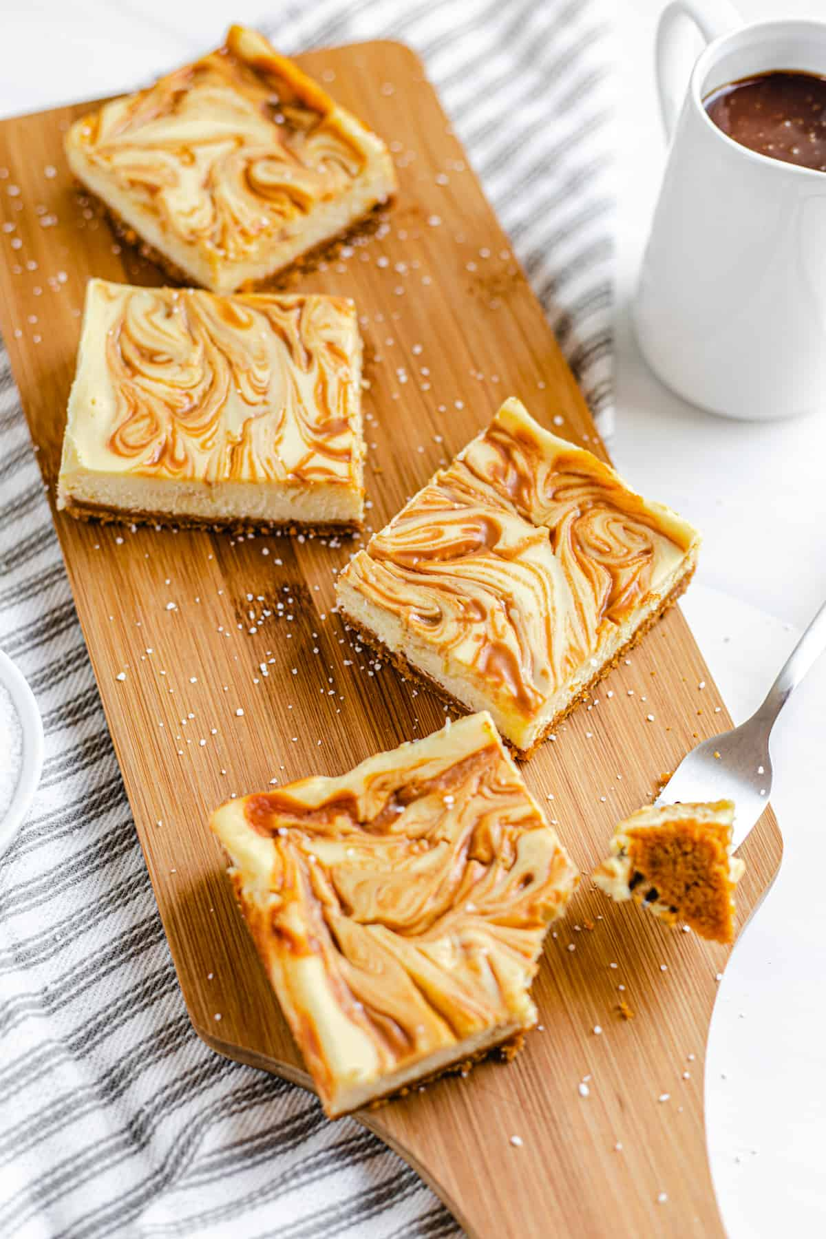 cheesecake bars on a wooden board with pitcher of caramel next to it and bite taken out of the front bar