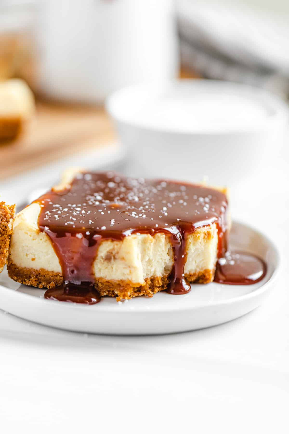 half-eaten caramel topped cheesecake bar on a small white plate