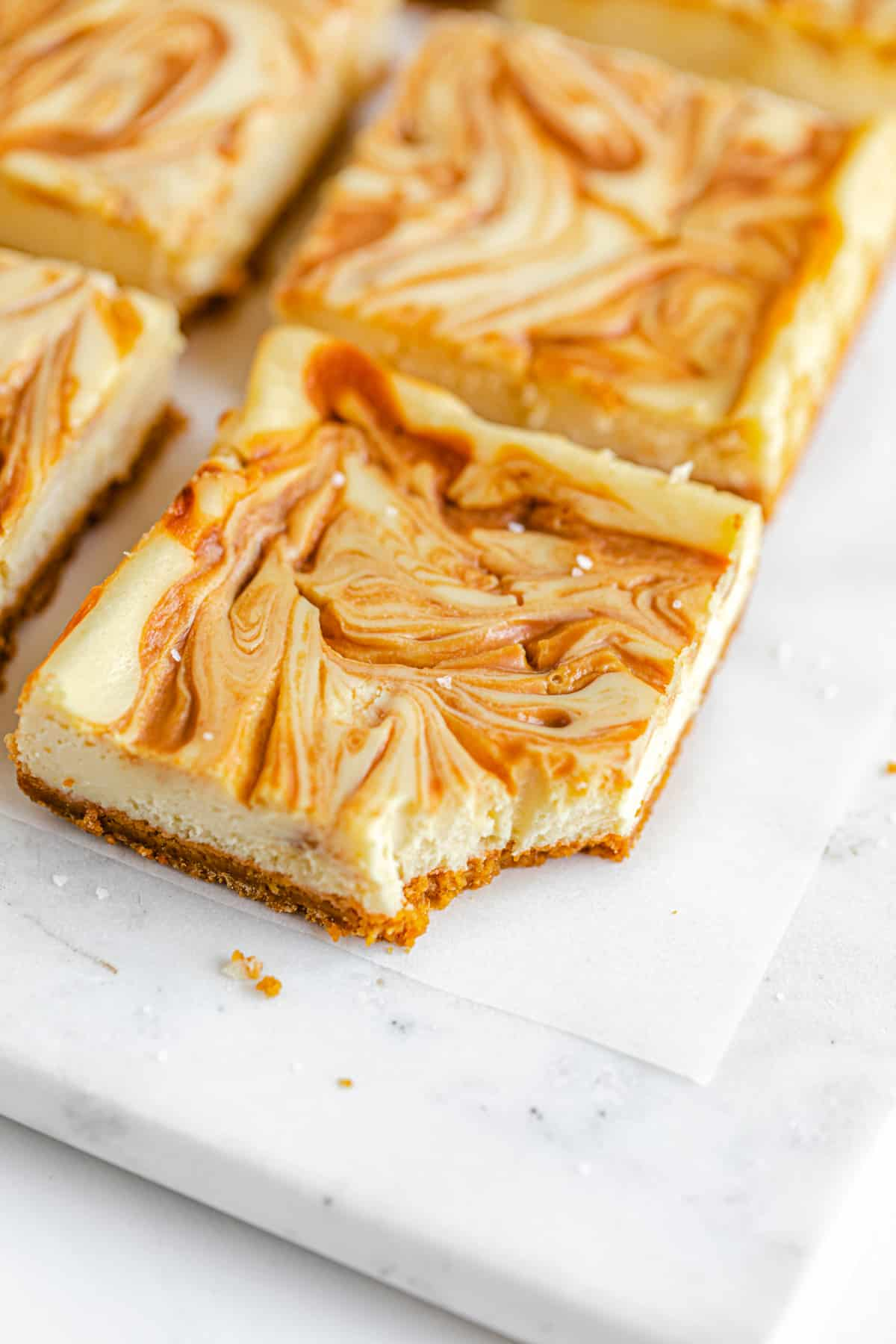 close up of cheesecake bars with caramel swirled on top in rows on a square marble board and a bite taken out the front bar